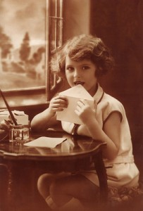 Young girl sealing the envelope of her letter
